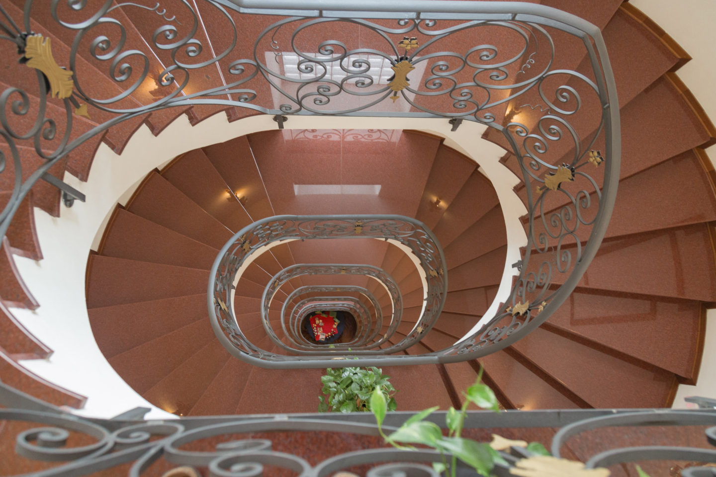 downward look at oval shaped spiral staircase with brown stairs and black delicate railings