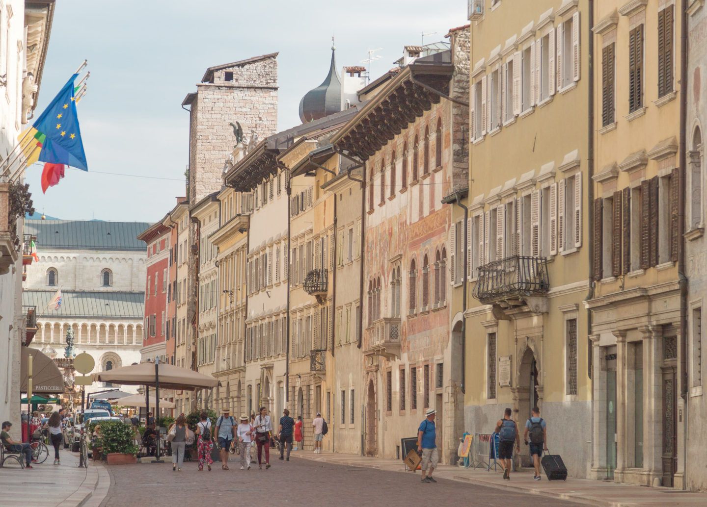 street scene in trento of faded colorful building facades and some people walking on the streets